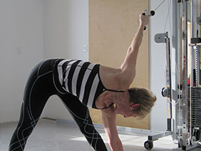 Woman going resistance training while reaching towards toes