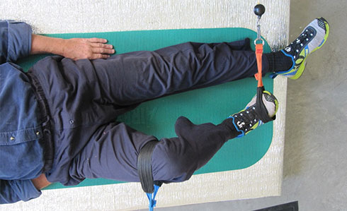 Man on mat on floor receiving Platypus METT therapy for his knee pain condition