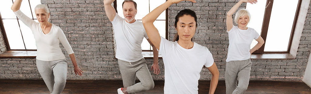 Four people doing a yoga pose for improved balance