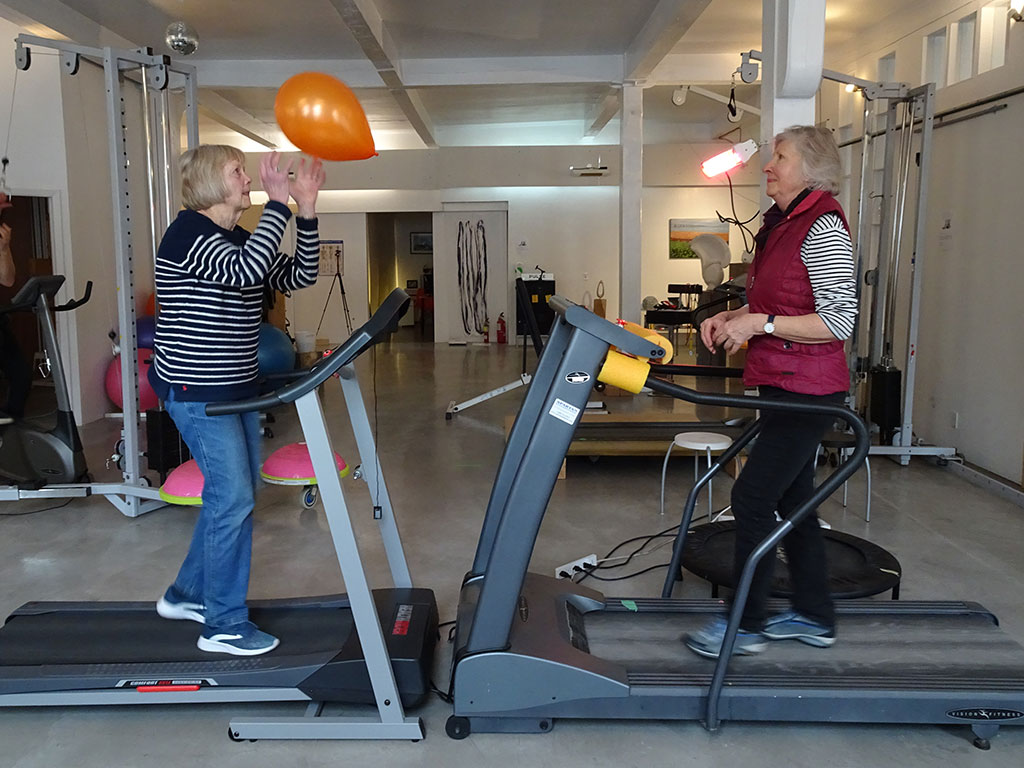 Women walking on treadmills passing a balloon back and forth