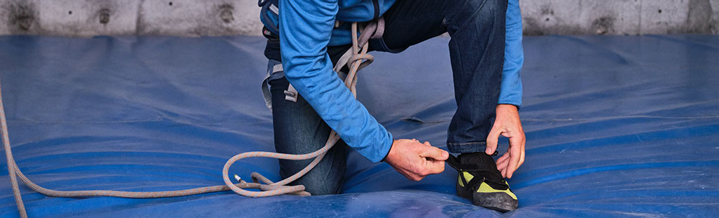 Man prepares himself for rock climbing by tightening his shoes
