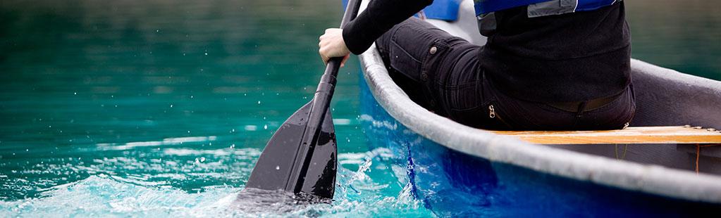 Person kayaking inside a blue kayak
