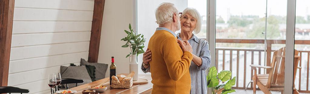 Older couple embrace near romantic dinner setting