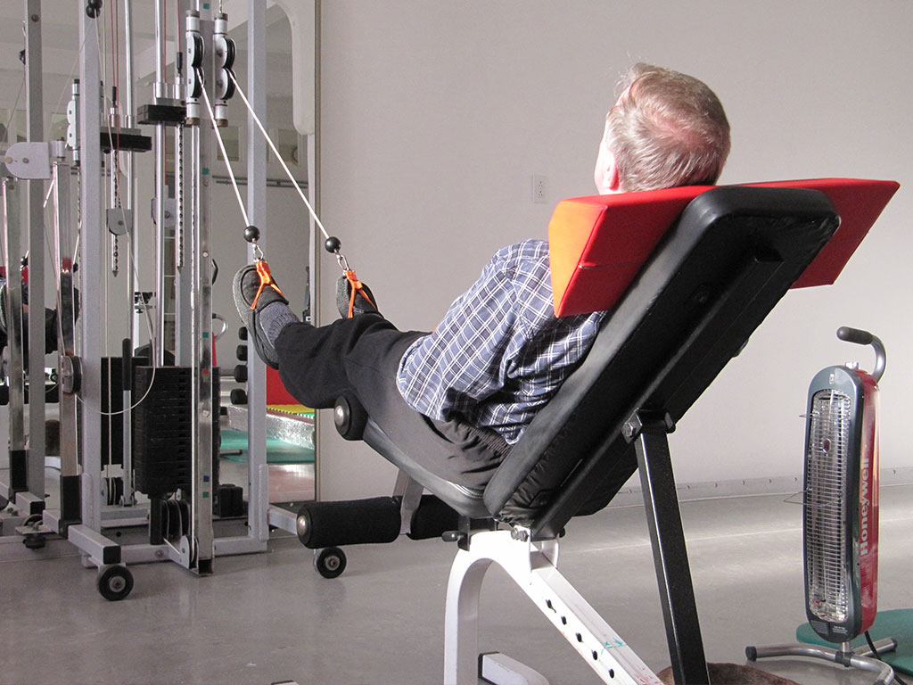 Man in half laying position on weight bench doing leg resistance training