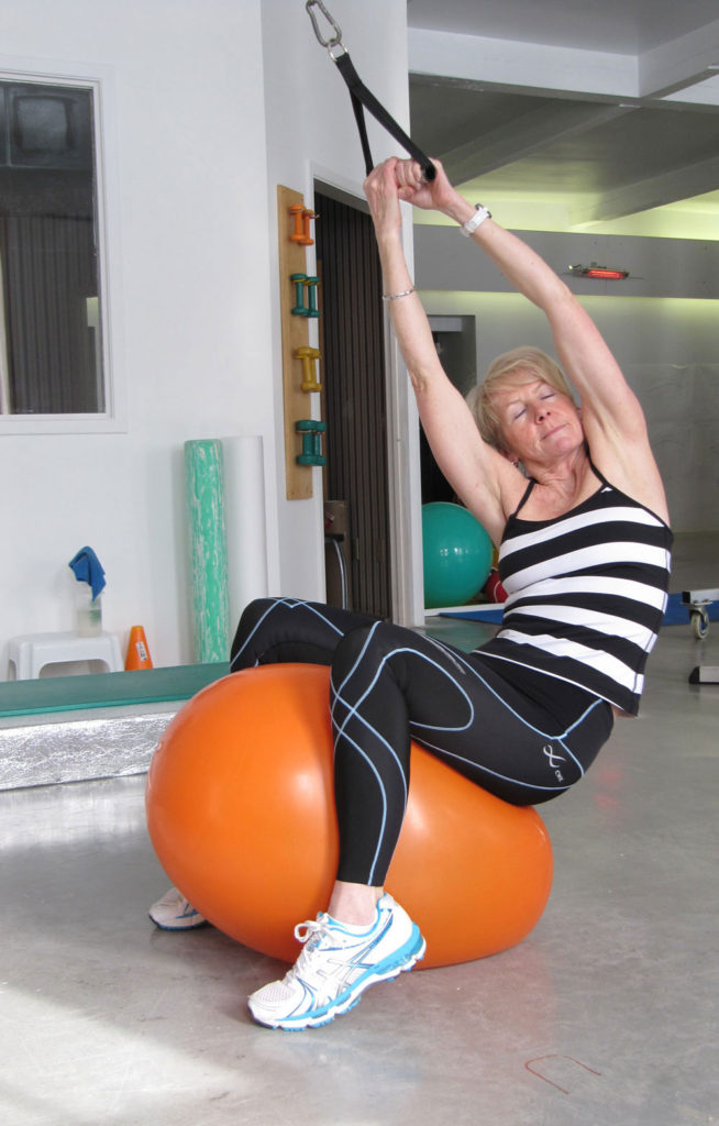 Woman sitting on orange exercise ball side stretching with exercise band